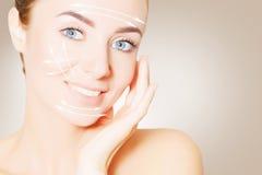 更新皮肤 妇女与举的标记的面孔画象 库存图片