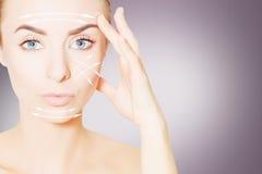 更新皮肤concpet 妇女与举的标记的面孔画象 库存图片