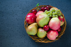 新秋天结果实-成熟苹果、梨、葡萄和李子在一块柳条木板材 背景蓝色黑暗的无限 收获概念 图库摄影