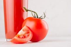 新红色蕃茄饮料和稀烂蕃茄与水多的片断在轻的软的白色木桌,拷贝空间,特写镜头上 免版税库存照片