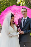 新结婚的夫妇在一把桃红色伞下 免版税库存照片