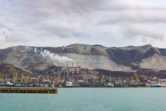 新罗西斯克货物口岸和JSC Novoroscement水泥植物的抽烟的烟囱全景在Markotkh背景中赶走了 免版税图库摄影