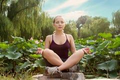 新美丽的妇女执行瑜伽并且在有莲花的公园思考 库存照片