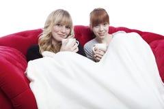 新美丽的白肤金发和红发女孩获得温暖在盖子之下 免版税图库摄影