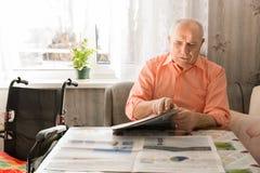 更新老人读书报纸在表上 免版税库存图片