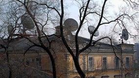 新老 一个老豪宅的屋顶的看法与许多卫星盘的 免版税库存照片