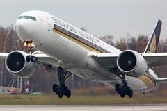 新航离开在多莫杰多沃国际机场的波音777-300 9V-SWR 免版税库存照片