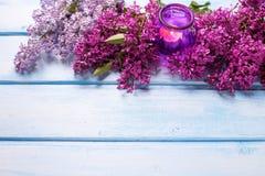 新芳香淡紫色花和蜡烛在蓝色木backgroun 图库摄影