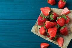 新草莓和羊皮纸在木背景,空间文本的和顶视图 夏天甜点果子 免版税库存图片