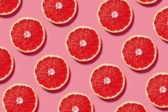 新葡萄柚切片的五颜六色的果子样式在桃红色背景的 免版税库存照片