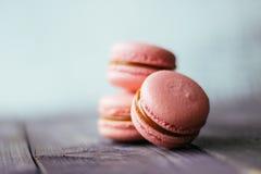 新被烘烤的紫色桃红色蛋白杏仁饼干酥皮点心曲奇饼macarons,在零售店显示,关闭的通心面,低角度视图 库存照片