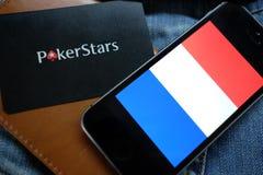 新西伯利亚,俄罗斯- 2016年12月13日:法国和商标在牛仔裤背景的Pokerstars旗子  图库摄影