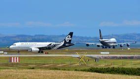 新西兰航空公司乘出租车的空中客车A320,当新航波音747-400货轮在奥克兰国际机场时离开 免版税库存照片