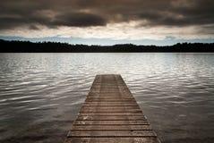 新西兰-木跳船主角到一个空的湖里在多云早晨 免版税库存图片