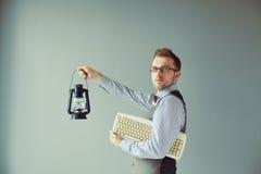 新计算机人拿着关键董事会和烛台 免版税库存图片