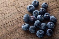 新近地摘的蓝莓在木背景中 与绿色叶子的水多和新鲜的蓝莓在土气桌上 免版税库存图片
