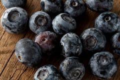新近地摘的蓝莓在木背景中 与绿色叶子的水多和新鲜的蓝莓在土气桌上 库存图片