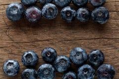 新近地摘的蓝莓在木背景中 水多和新鲜的蓝莓 免版税库存照片