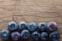新近地摘的蓝莓在木背景中 免版税库存图片