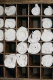 新近地被洗涤的蓬松毛巾在一个木洗脸台滚动 在慢动作的受欢迎的手段装饰 库存图片