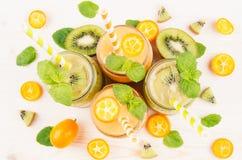新近地被混和的橙色金桔和绿色猕猴桃圆滑的人在玻璃瓶子有秸杆的,薄荷的叶子,裁减成熟莓果,顶视图,关闭 免版税库存照片