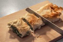 新近地被烘烤的传统塞尔维亚乳酪菠菜饼卷切与在木切板的被加锯齿的面包刀 图库摄影
