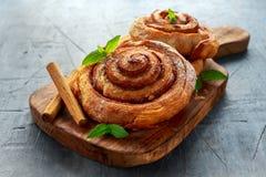 新近地被烘烤的传统甜桂香劳斯,在木板的漩涡 库存照片