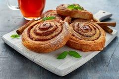 新近地被烘烤的传统甜桂香劳斯,在白色木板的漩涡用热的红茶和薄菏 免版税图库摄影