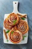 新近地被烘烤的传统甜桂香劳斯,在白色木板的漩涡 免版税库存图片