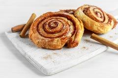 新近地被烘烤的传统甜桂香劳斯,在白色木板的漩涡 库存图片
