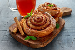 新近地被烘烤的传统甜桂香劳斯,漩涡用热的红茶和薄菏 库存图片