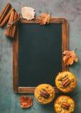 新近地被烘烤的南瓜松饼和肉桂条有空的黑板的 库存照片