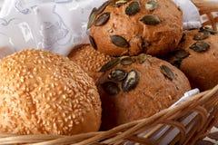 新近地被烘烤的卷和面包在一个篮子在桌上 图库摄影