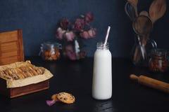 新近地被烘烤的巧克力杏仁芯片曲奇饼和瓶用牛奶 图库摄影