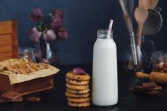 新近地被烘烤的巧克力杏仁芯片曲奇饼和瓶用牛奶 库存图片