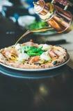 新近地被烘烤的意大利薄饼用火腿,朝鲜蓟在餐馆服务 库存照片