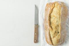 新近地被烘烤的手制作了在白色亚麻制毛巾的土气面包大面包与在织地不很细具体桌面的刀子 最低纲领派样式 图库摄影