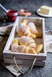 新近地被烘烤的新月形面包服务用山莓果酱和黄油 图库摄影