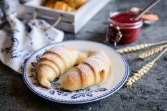 新近地被烘烤的新月形面包服务用山莓果酱和黄油 免版税库存照片