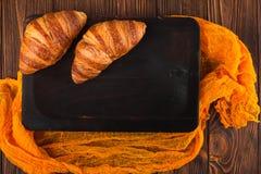 新近地被烘烤的新月形面包果酱,咖啡在白色杯子的在棕色木背景 法国早餐新鲜的酥皮点心早餐 库存照片