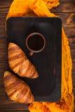 新近地被烘烤的新月形面包果酱,咖啡在白色杯子的在棕色木背景 法国早餐新鲜的酥皮点心早餐 免版税库存照片
