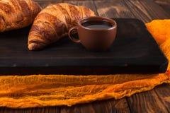 新近地被烘烤的新月形面包果酱,咖啡在白色杯子的在棕色木背景 法国早餐新鲜的酥皮点心早餐 免版税图库摄影