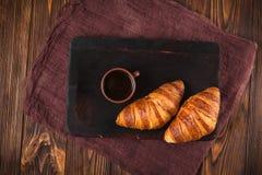 新近地被烘烤的新月形面包果酱,咖啡在白色杯子的在棕色木背景 法国早餐新鲜的酥皮点心早餐 库存图片