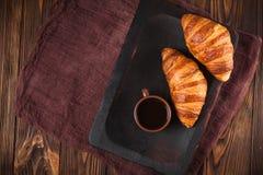 新近地被烘烤的新月形面包果酱,咖啡在白色杯子的在棕色木背景 法国早餐新鲜的酥皮点心早餐 图库摄影