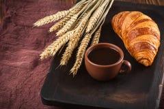 新近地被烘烤的新月形面包果酱,咖啡在白色杯子的在棕色木背景 法国早餐新鲜的酥皮点心早餐 免版税库存图片