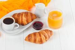 新近地被烘烤的新月形面包橙汁,果酱,杯子在白色木背景的无奶咖啡 法国早餐新鲜的酥皮点心为mo 免版税库存照片