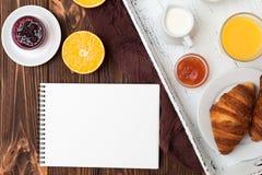 新近地被烘烤的新月形面包,橙汁,新鲜水果,在棕色木背景的果酱 法国早餐新鲜的酥皮点心为早晨 免版税库存照片