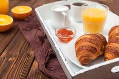 新近地被烘烤的新月形面包,橙汁,新鲜水果,在棕色木背景的果酱 法国早餐新鲜的酥皮点心为早晨 图库摄影