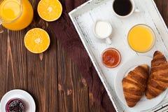 新近地被烘烤的新月形面包,橙汁,新鲜水果,在棕色木背景的果酱 法国早餐新鲜的酥皮点心为早晨 库存照片