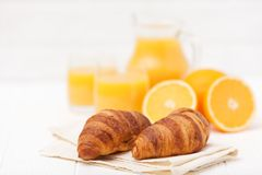 新近地被烘烤的新月形面包,橙汁,新鲜水果,在白色木背景的果酱 法国早餐新鲜的酥皮点心 图库摄影